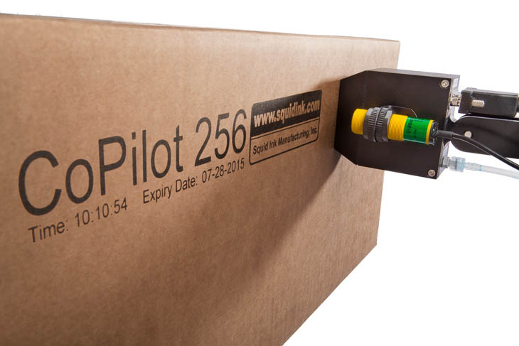 The Squid Ink CoPilot 256 hi-resolution industrial inkjet printer printing date codes, time codes, and logos on a corrugated cardboard box