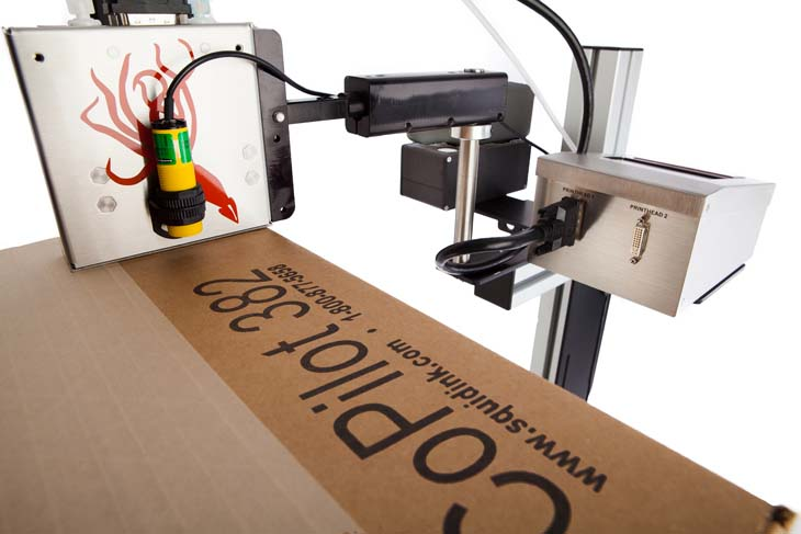 The Squid Ink CoPilot 382 hi-resolution industrial inkjet printer coding and marking on a corrugated cardboard box in the down shooter position